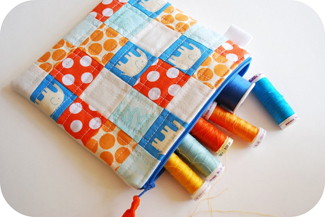 Patchwork pouch in blue, orange and white cotton with blue zipper open showing colorful spools of thread inside.